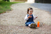 Little cute baby girl playing with soap bubbles in summer park — Stock Photo