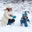 Mother and toddler boy having fun with snow on winter day — Stock Photo #30577963