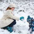 Mother and toddler boy having fun with snow on winter day — Stock Photo #30577967