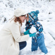 Mother and toddler boy having fun with snow on winter day — Stock Photo #30578005