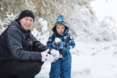 Father and toddler boy having fun with snow on winter day — Stock Photo