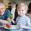 Little toddler boy and his great grandmother eating watermelon a — Stock Photo