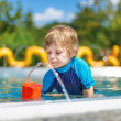 Cute toddler playing with water by the outdoor swimming pool  — Stock Photo