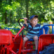 Stock Photo: Portrait of little blond boy in tractor in summer