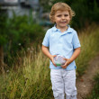Beautiful little boy walking on a country road  — Stock Photo