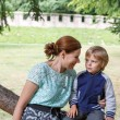 Young woman sitting on tree with her little son and speaking — Stock Photo #31065439
