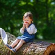 Little cute baby girl eating fruit in forest — Stock Photo #31066031