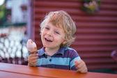 Little blond boy eating yellow ice cream — Stock Photo