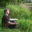 Young handsome man sitting near forest lake and relaxing — Stock Photo
