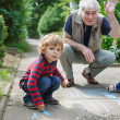 Stock Photo: Two little sibling boys and happy grandfather painting with chal
