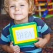 Little toddler boy with painting board writes his first word — Stock Photo #31982269