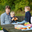 Young father and two little boys picnicking in the park — Stock Photo #31982299