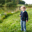 Little blond boy near forest lake, on summer evening — Stock Photo #31982547
