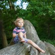 Little cute toddler boy having fun on tree in forest — Stock Photo