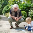 Stock Photo: Little blond toddler boy and happy grandfather painting with cha