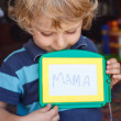 Little toddler boy with painting board writes his first word — Stock Photo #31983209