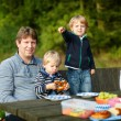 Young father and two little boys picnicking in the park — Stock Photo