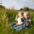 Two little brother boys playing near forest lake on summer eveni — Stock Photo