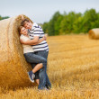 Young couple in love on yellow hay field on summer evening.  — Stock Photo