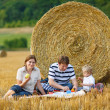 Happy family of three picnicking on yellow hay field in summer.  — Stock Photo