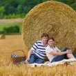 Stock Photo: Young couple picknicking on yellow hay field on summer evening.