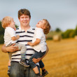 Young father and two little brother boys having fun on yellow ha — Stock Photo