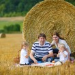 Stock Photo: Happy family of four picnicking on yellow hay field in summer.