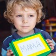 Little toddler boy with painting board writes his first word — Stock Photo