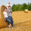 Stock Photo: Happy family of three on yellow hay field in summer.