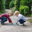Stock Photo: Two little sibling boys painting with chalk outdoors