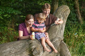 Family of three blowing soap bubbles together in summer forest — Stock Photo