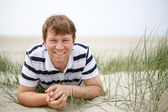 Young happy man relaxing on sand dunes of the beach of St.Peter — Stock Photo