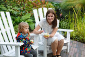 Young woman and little toddler boy eating ice cream outdoors — Stock Photo
