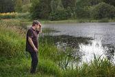 Jonge knappe man zitten in de buurt van bos meer en ontspannen — Stockfoto