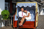 Beautiful indian bride and caucasian groom in beach chair — Stock Photo