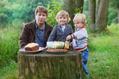 Young father and two little boys picnicking in nature forest nea — Stock Photo