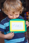 Little toddler boy with painting board writes his first word — Стоковое фото
