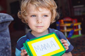 Little toddler boy with painting board writes his first word — Foto de Stock