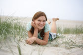 Young happy girl relaxing on sand dunes of the beach of St.Peter — Stock Photo