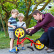 Stock Photo: Young mand two little sons repairing bicycle outdoors.