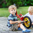 Stock Photo: Two little boys, siblings, repairing bicycle outdoors.