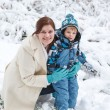 Young woman and her little son having fun with snow in winter fo — Stock Photo