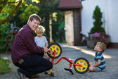 Portrait of two cute boys repairing bicycle wheel with father ou — Stock Photo