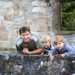 Stock Photo: Young mand his two little boys standing behind wall of old Ge
