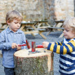 Two little sibling boys playing with hammer outdoors. — Photo