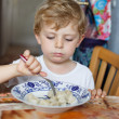 Cute toddler boy of three years eating pasta at home kitchen — Stock Photo