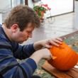Young man making halloween pumpkin — Stock Photo #33327849