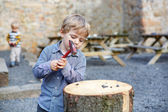 Little blond boy playing with hammer outdoors with brother. — Stock Photo