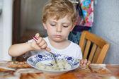 3 年の家庭の台所でパスタを食べるのかわいい幼児男の子 — ストック写真