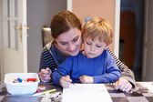 Little blond boy and his mother making together preschool homewo — Stock Photo